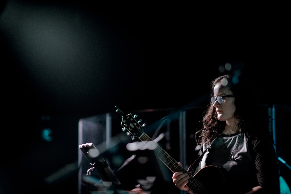 woman playing guitar on stage