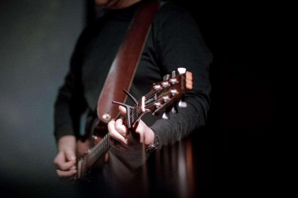 person playing brown guitar