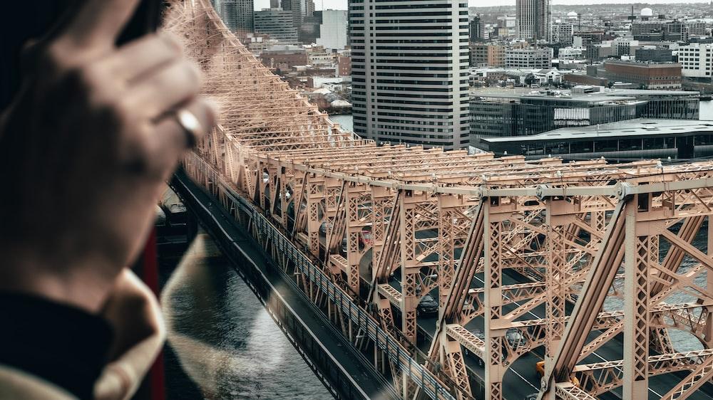 black and brown concrete bridge near city buildings