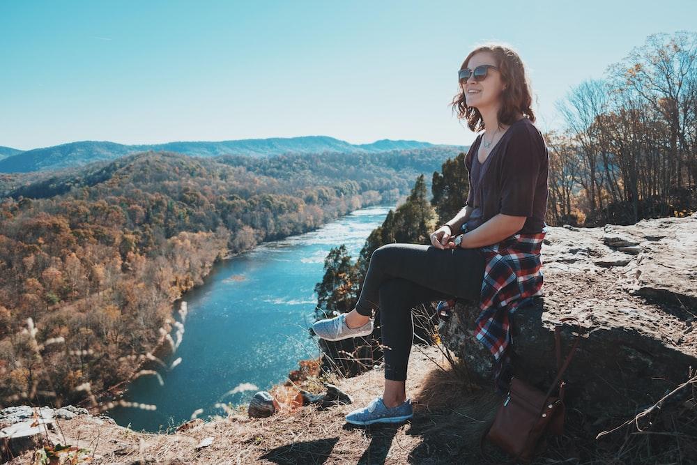 woman sitting on rocks during daytime