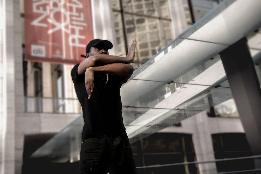 man in black swearing wearing baseball cap during daytime