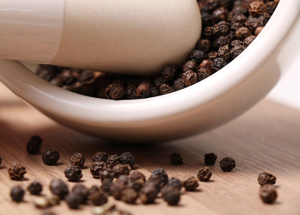 black pepper on white ceramic mortar and pestle
