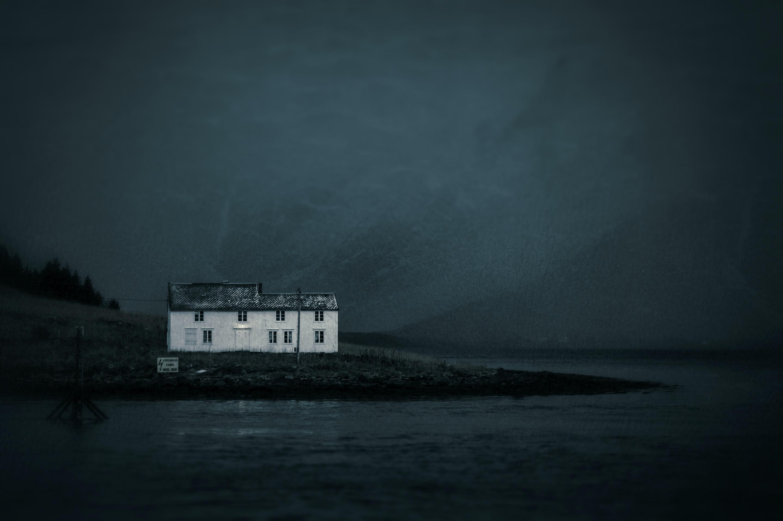 white concrete house beside shore