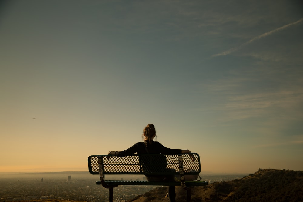 woman sitting on bench during daytime