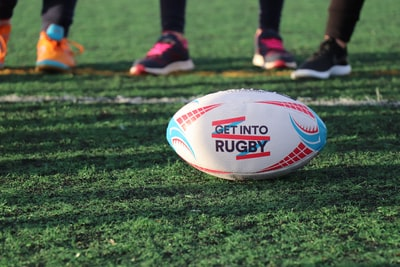 white, blue, and red football on green grass rugby teams background