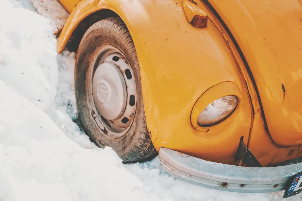 yellow Volkwagen car stack on snow