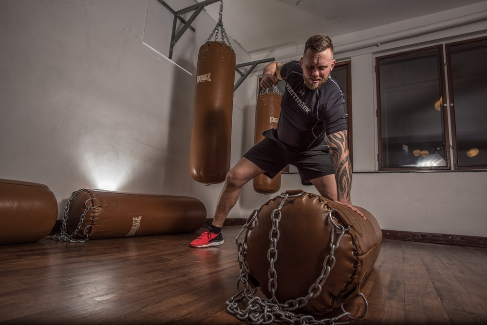 man punching brown leather heavy bag