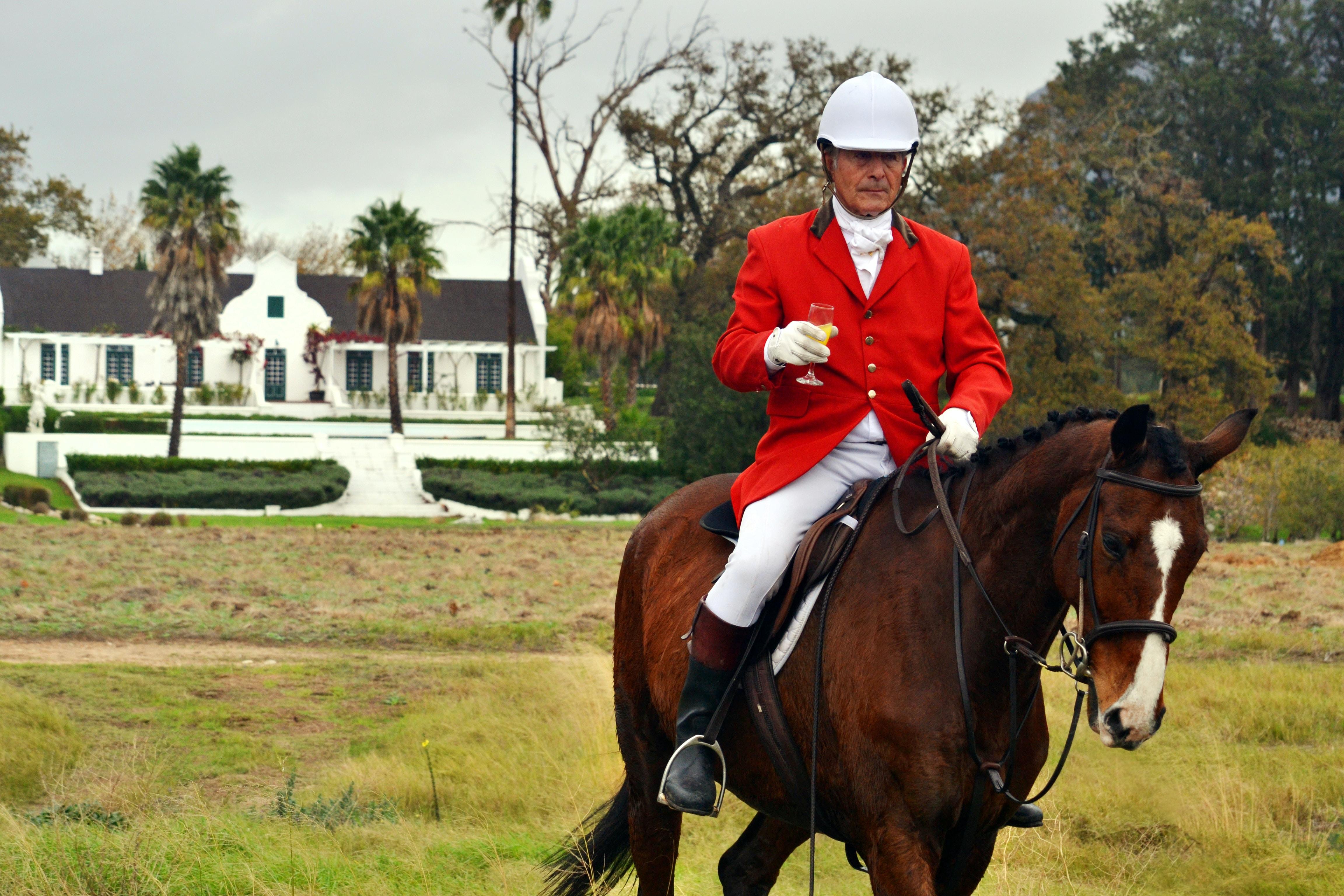 man riding horse on farm during daytime