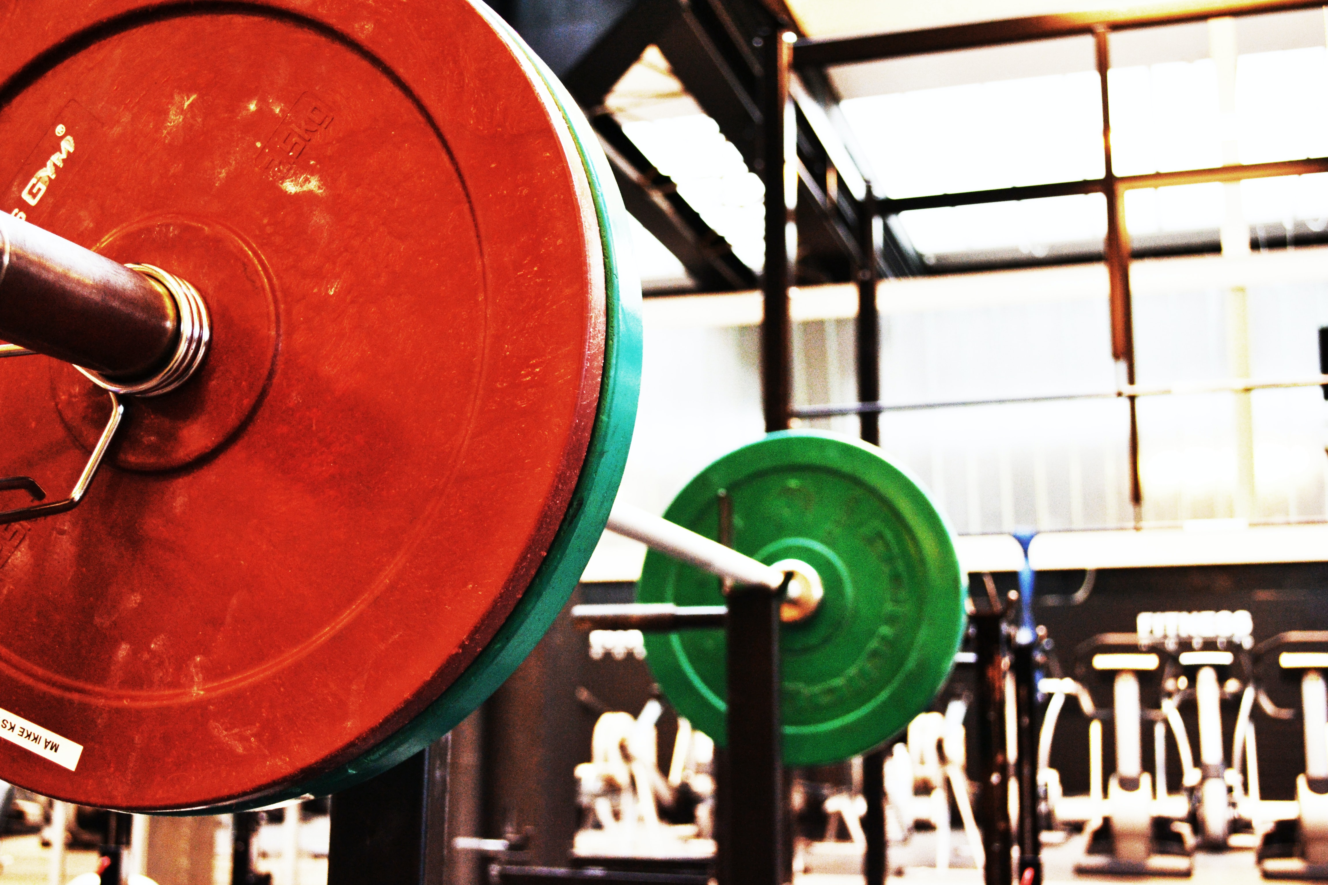 red and green barbell on rack