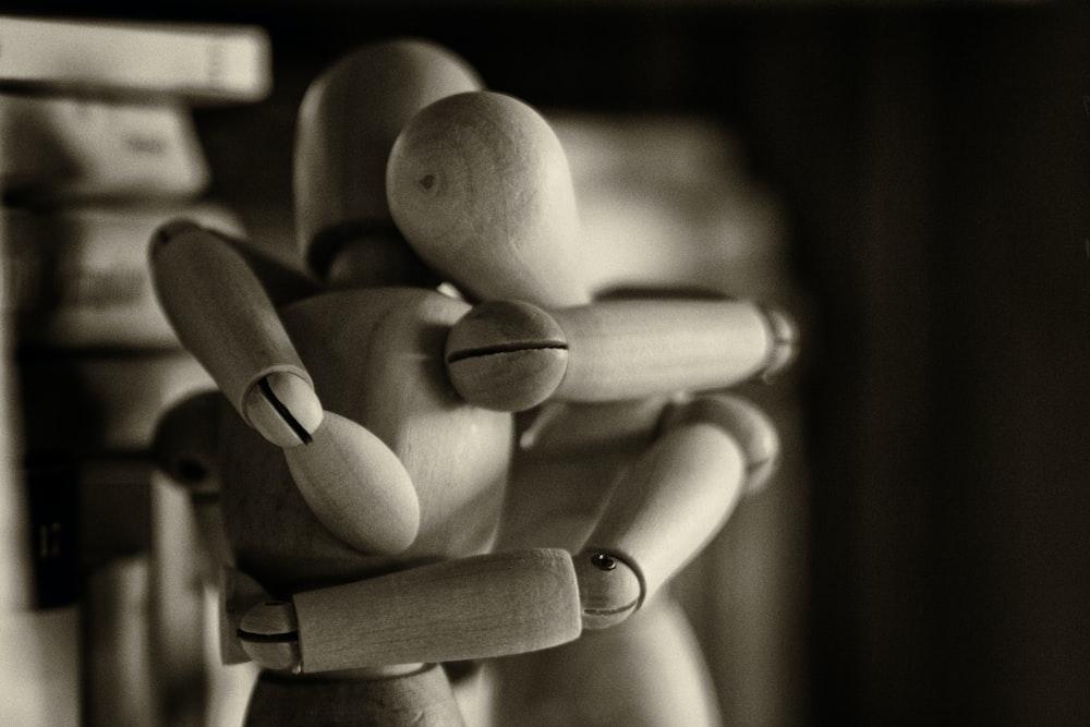 two wooden dummy hugging figures