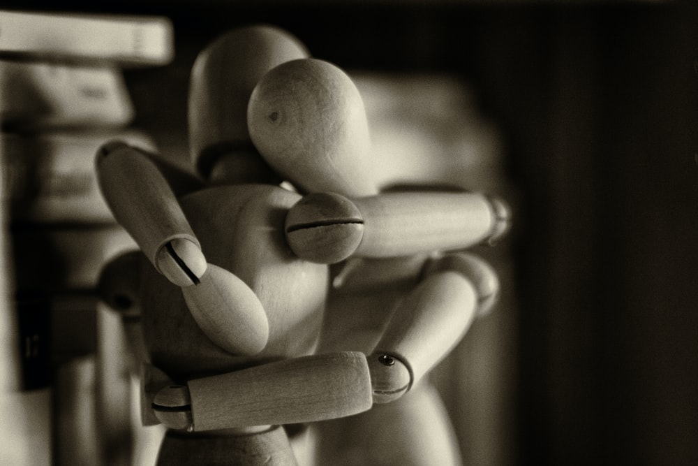 two wooden dummy hugging figures