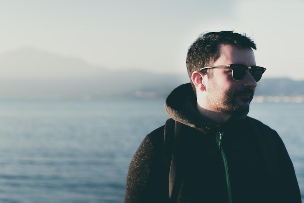 man wearing eyeglasses standing near body of water