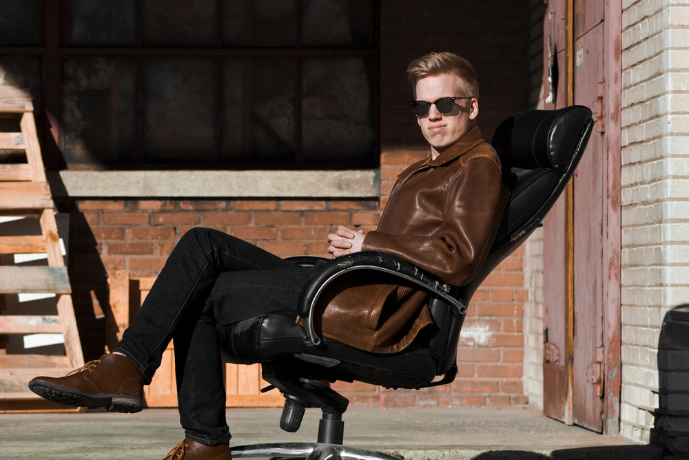 man sitting on black leather office rolling armchair