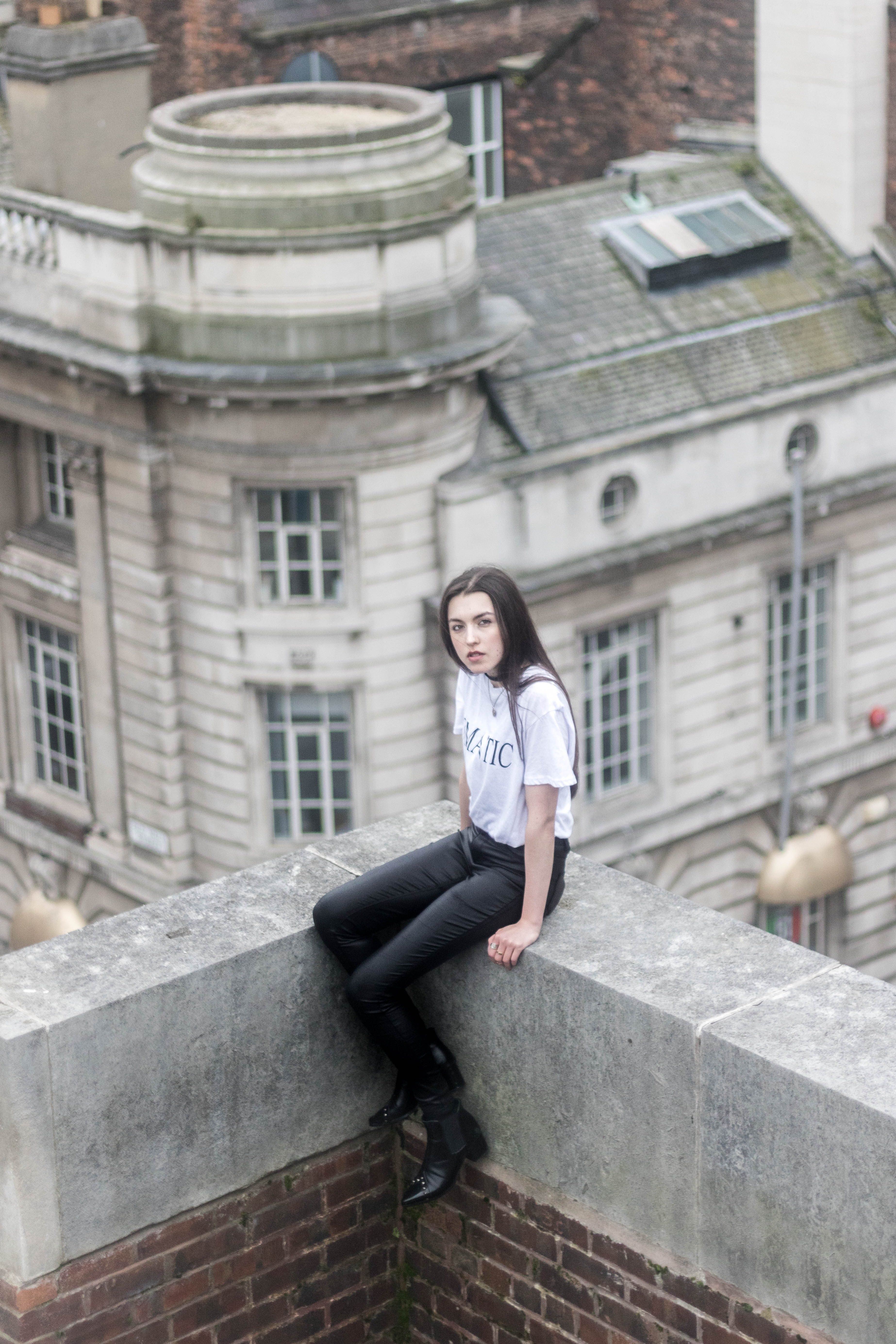 woman in white shirt sitting on top of building