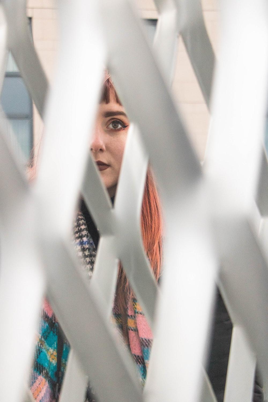 man peeping through white fence