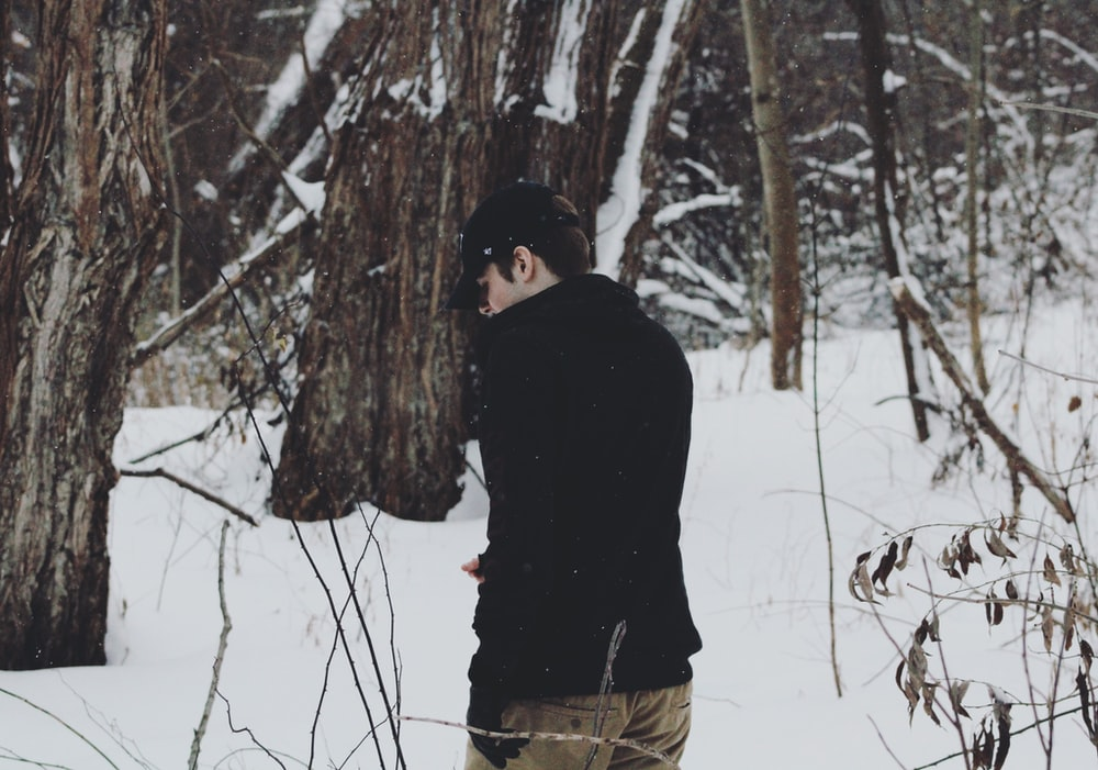 man wearing jack standing between trees with snow
