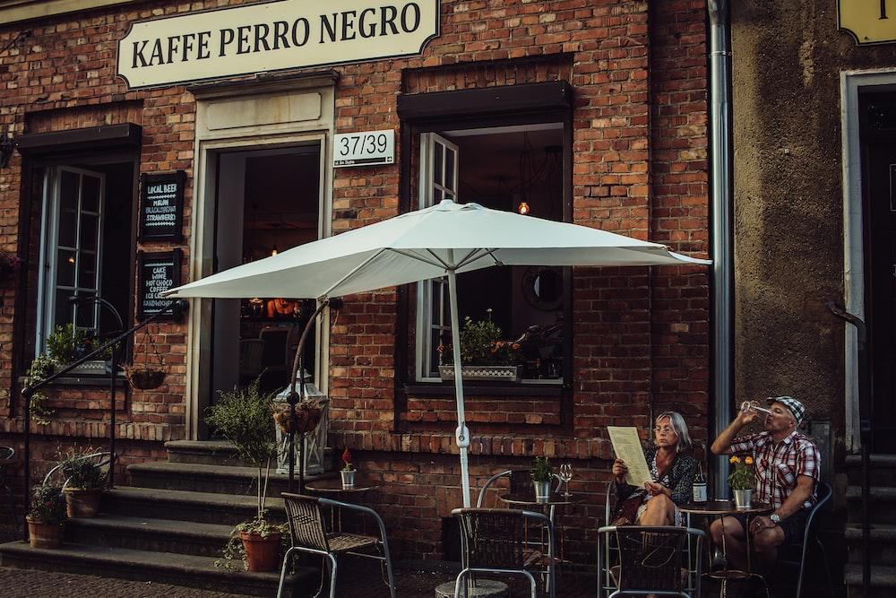 man and woman sitting on Kaffe Perro Negro patio