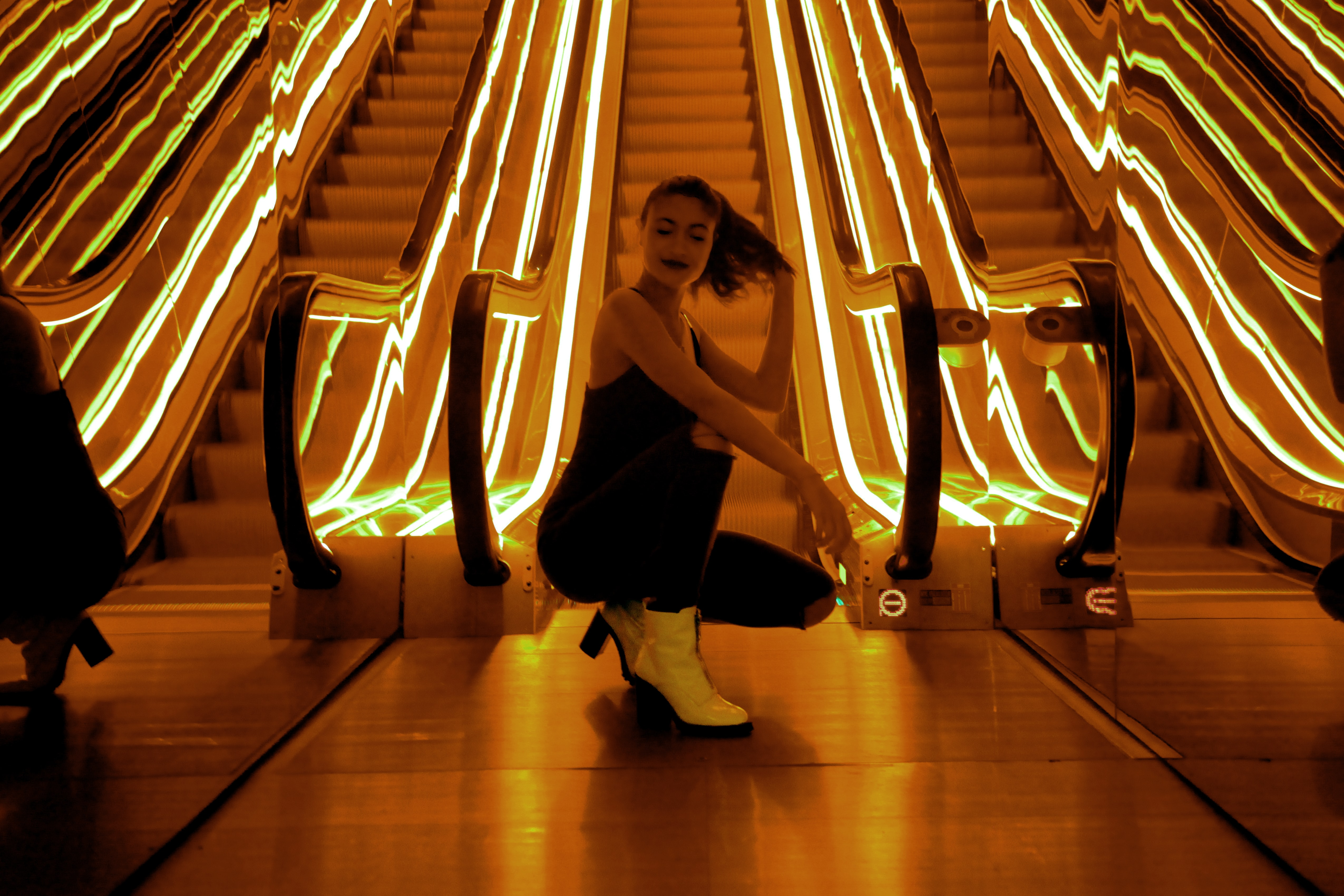 woman in front of lighted escalators