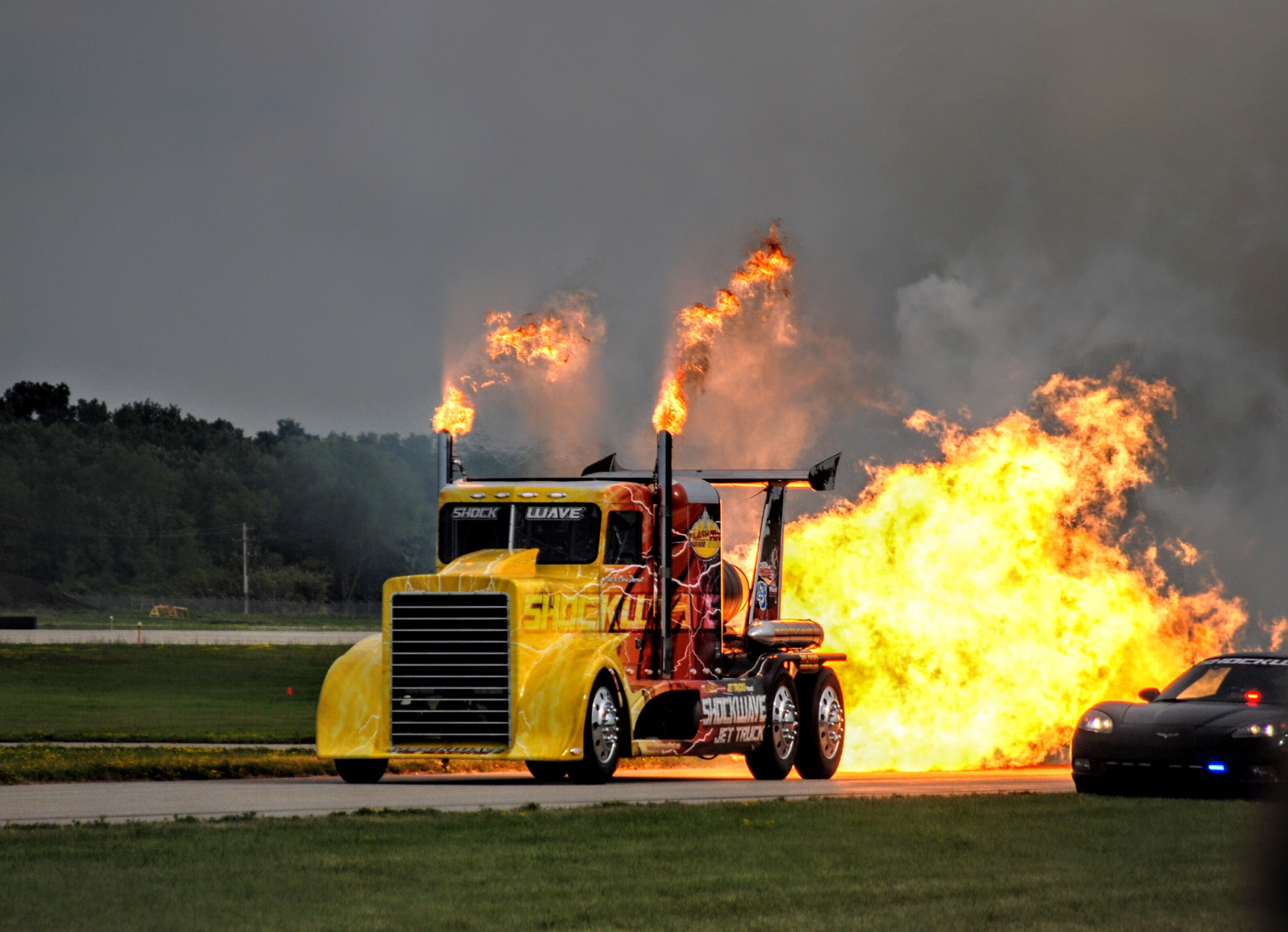yellow semi truck on fire behind