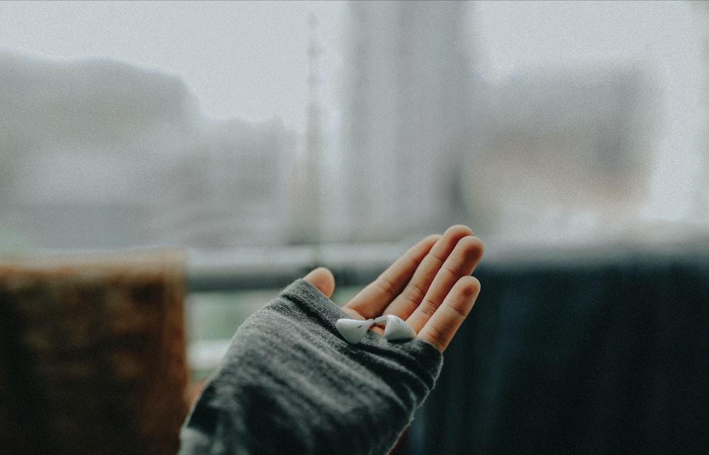left person's hand holding earphones