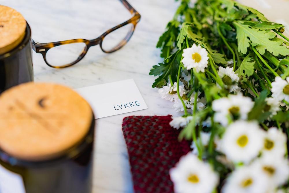 shallow focus photo of eyeglasses beside flower