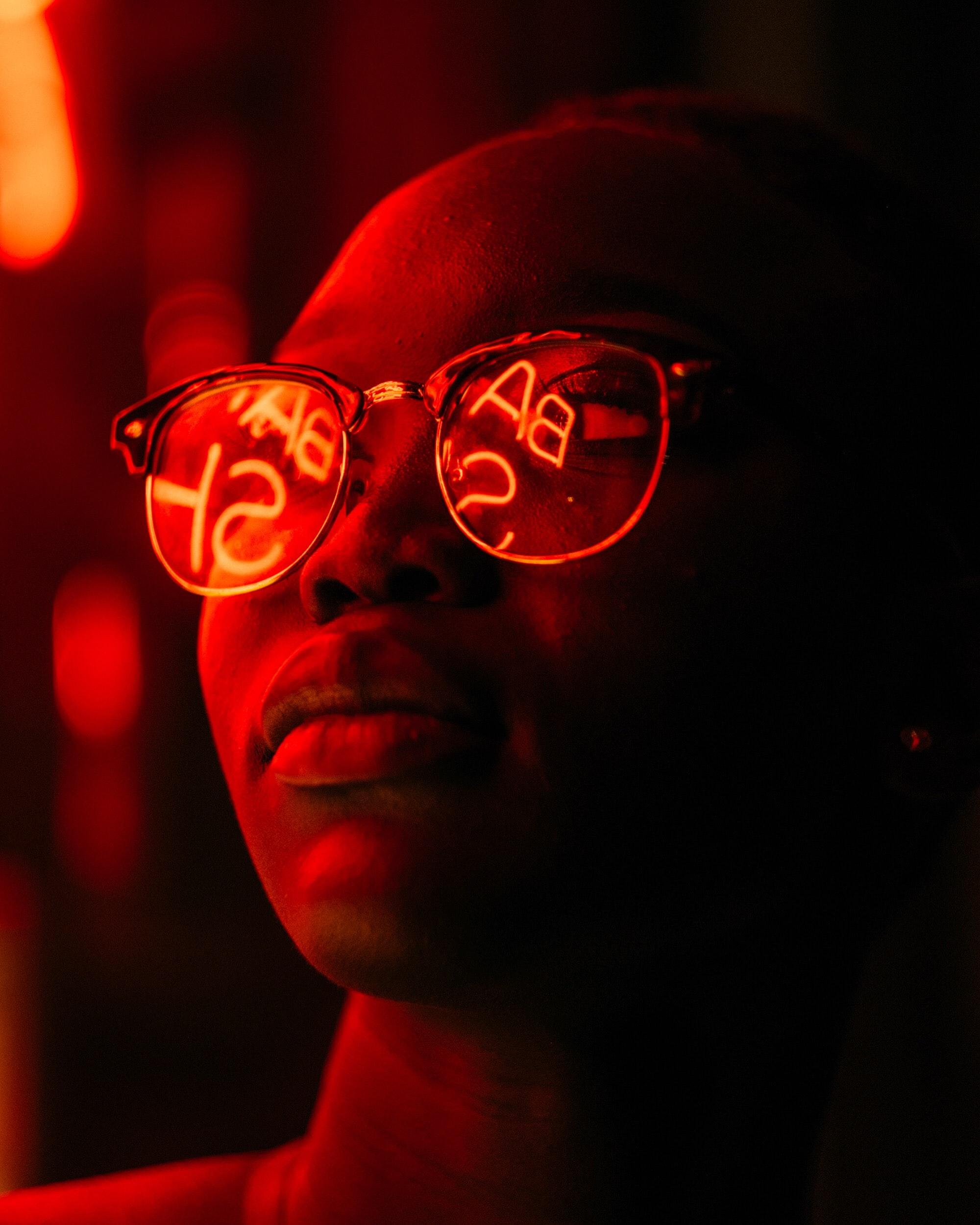 woman wearing eyeglasses with red LED signage reflection