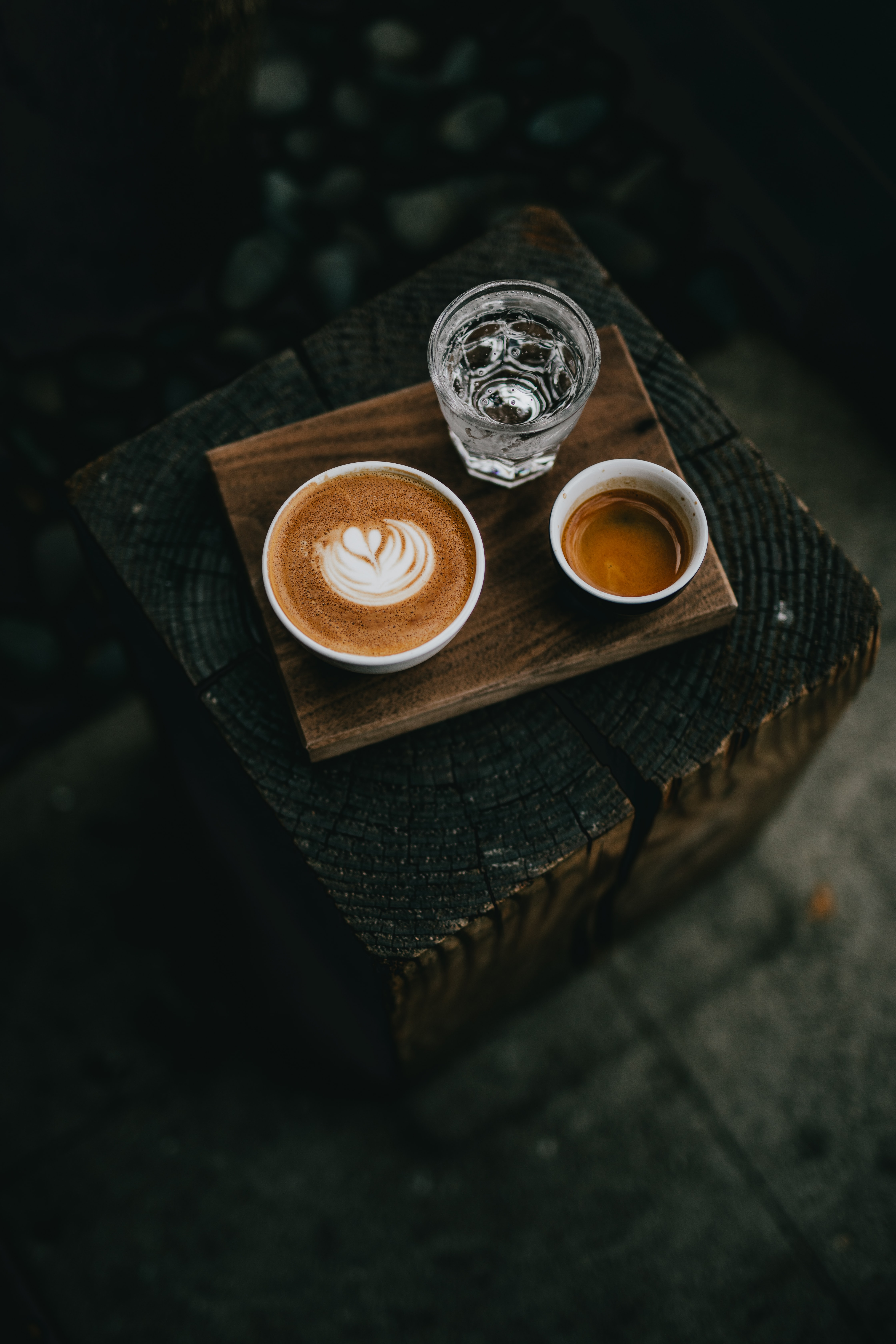 white ceramic cup filled with coffee beside glass of water