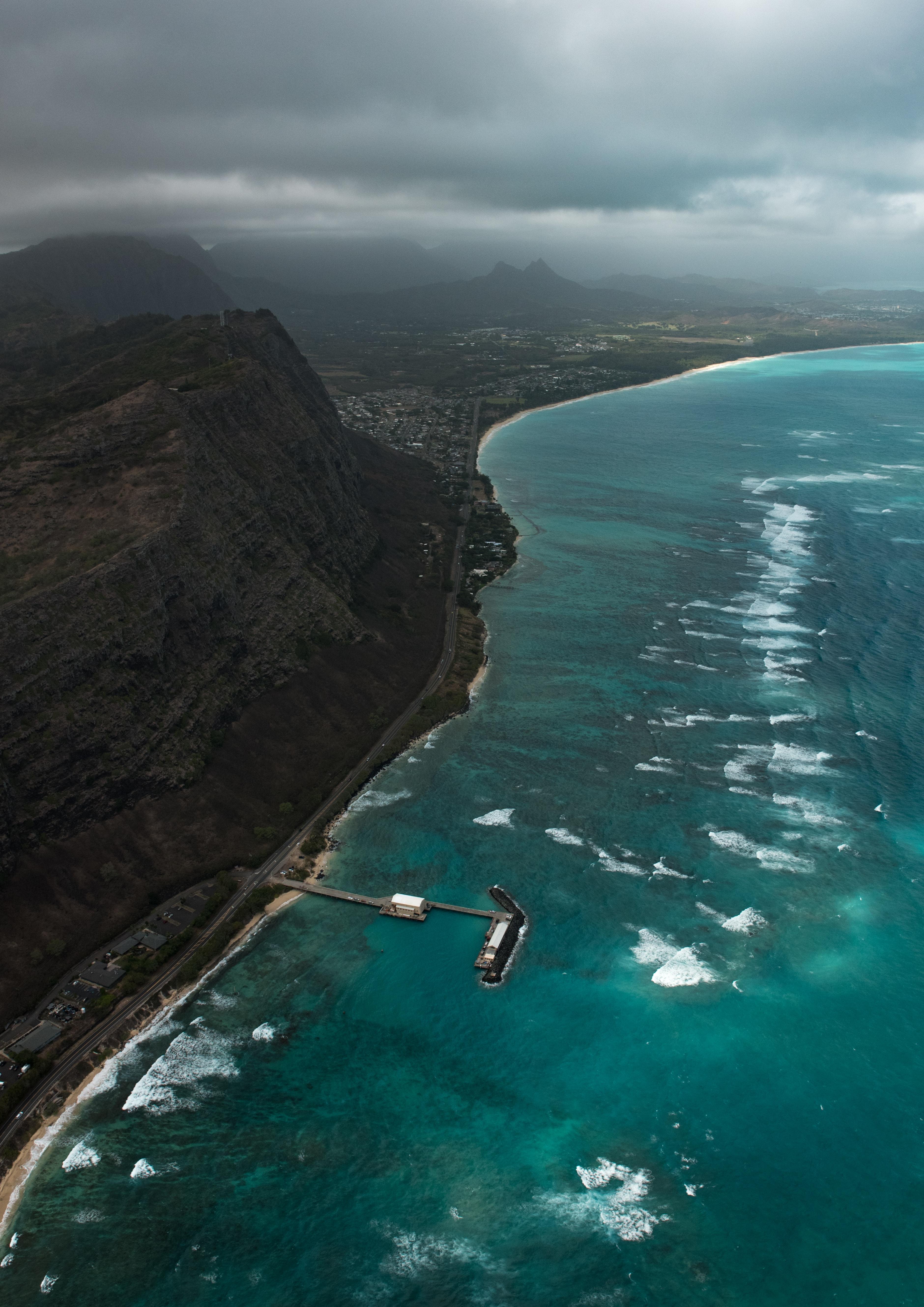 aerial photo of beach dock near cliff