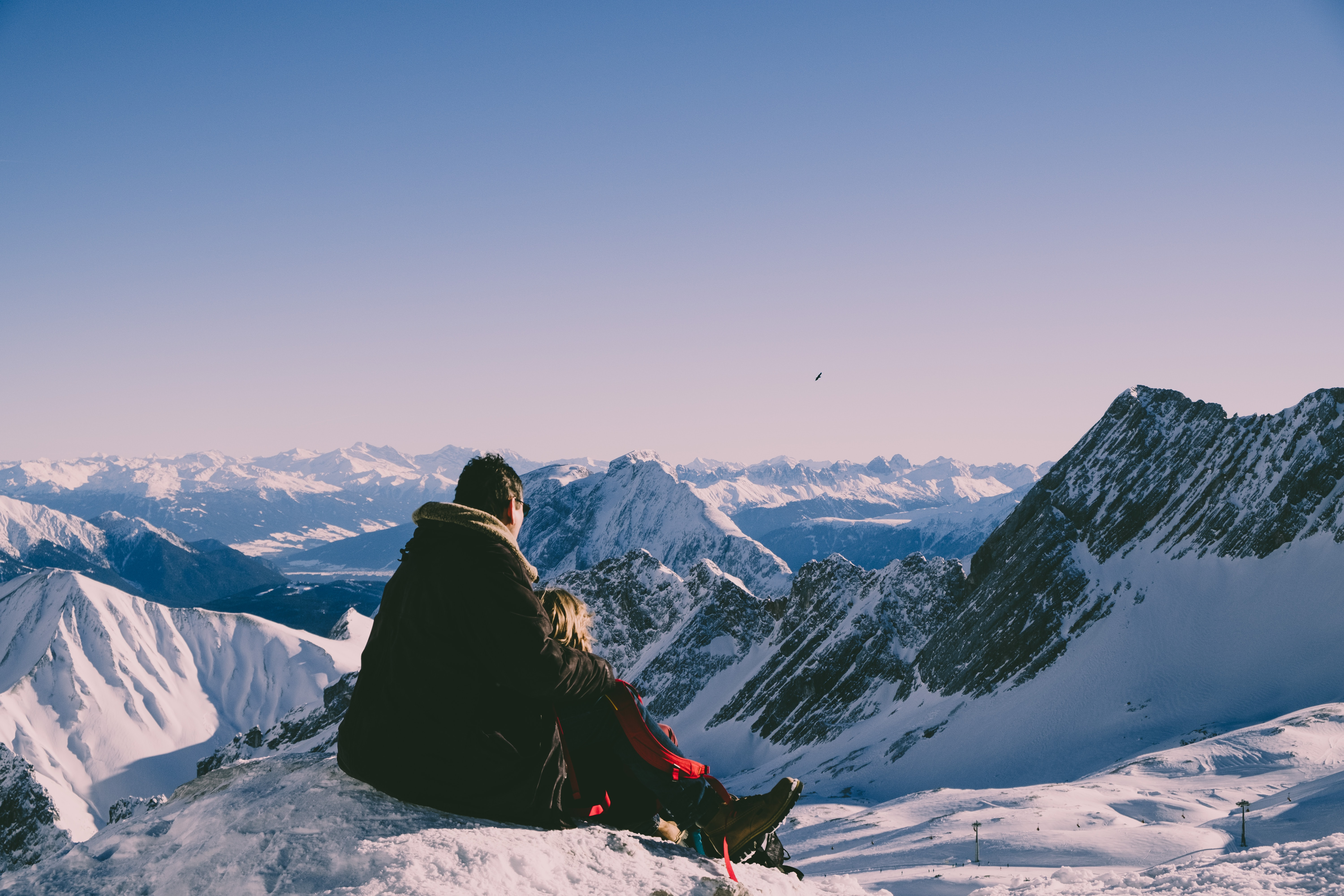 man and woman on top of peak