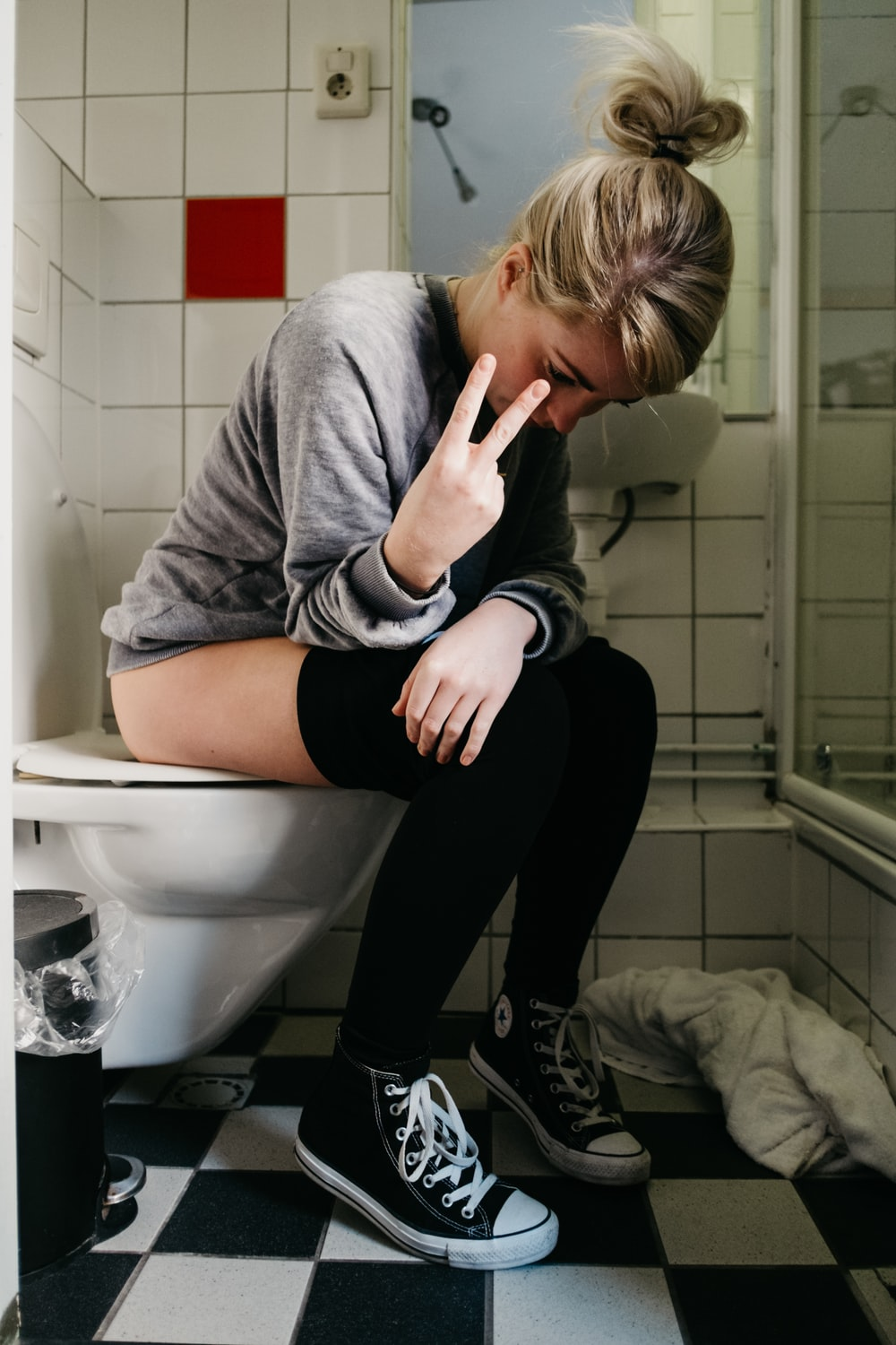 woman sitting on toilet bowl showing peace hand sign
