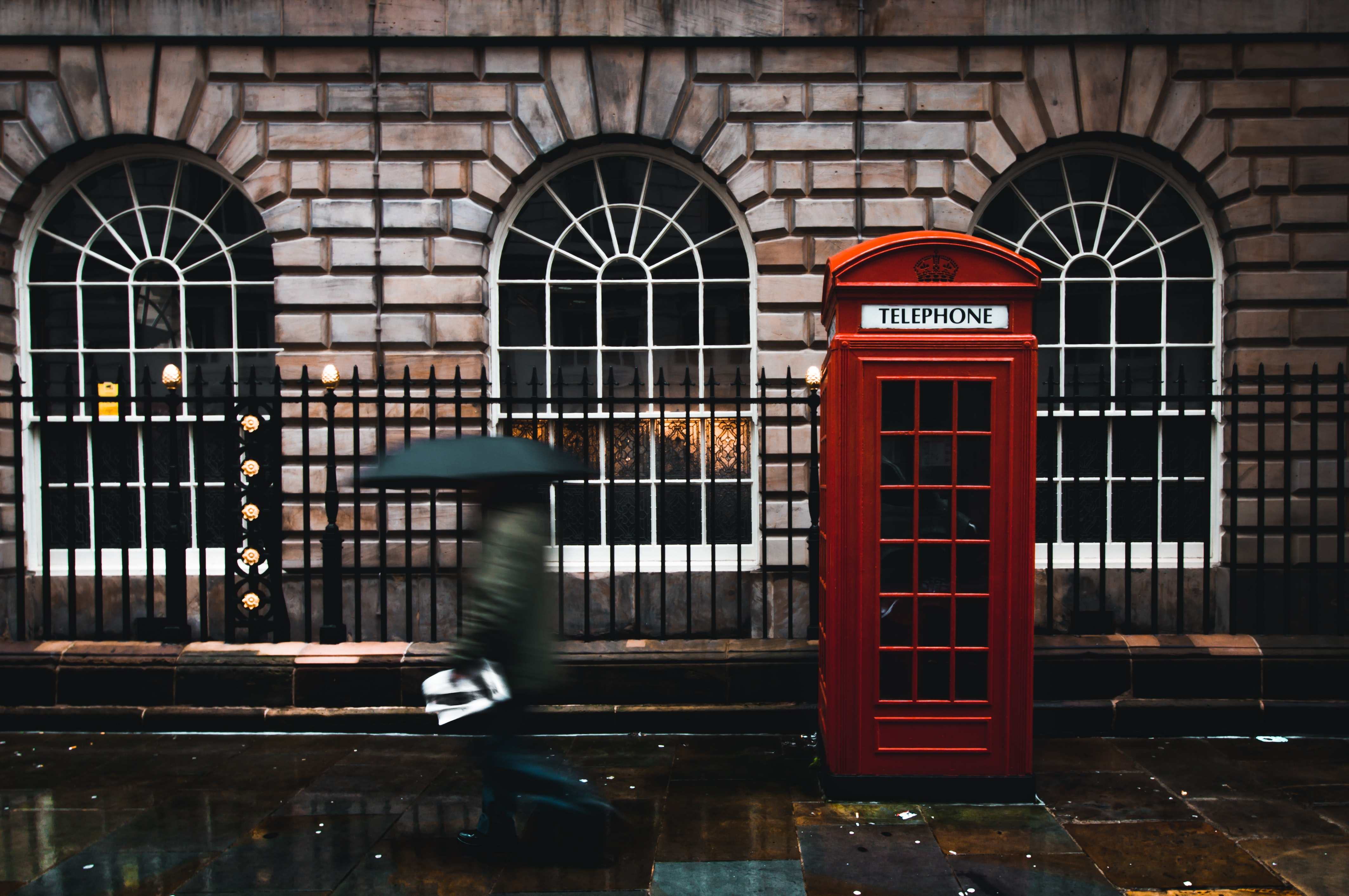 time lapse photography of woman walking on street while holding umbrella near London telephone booth beside wall