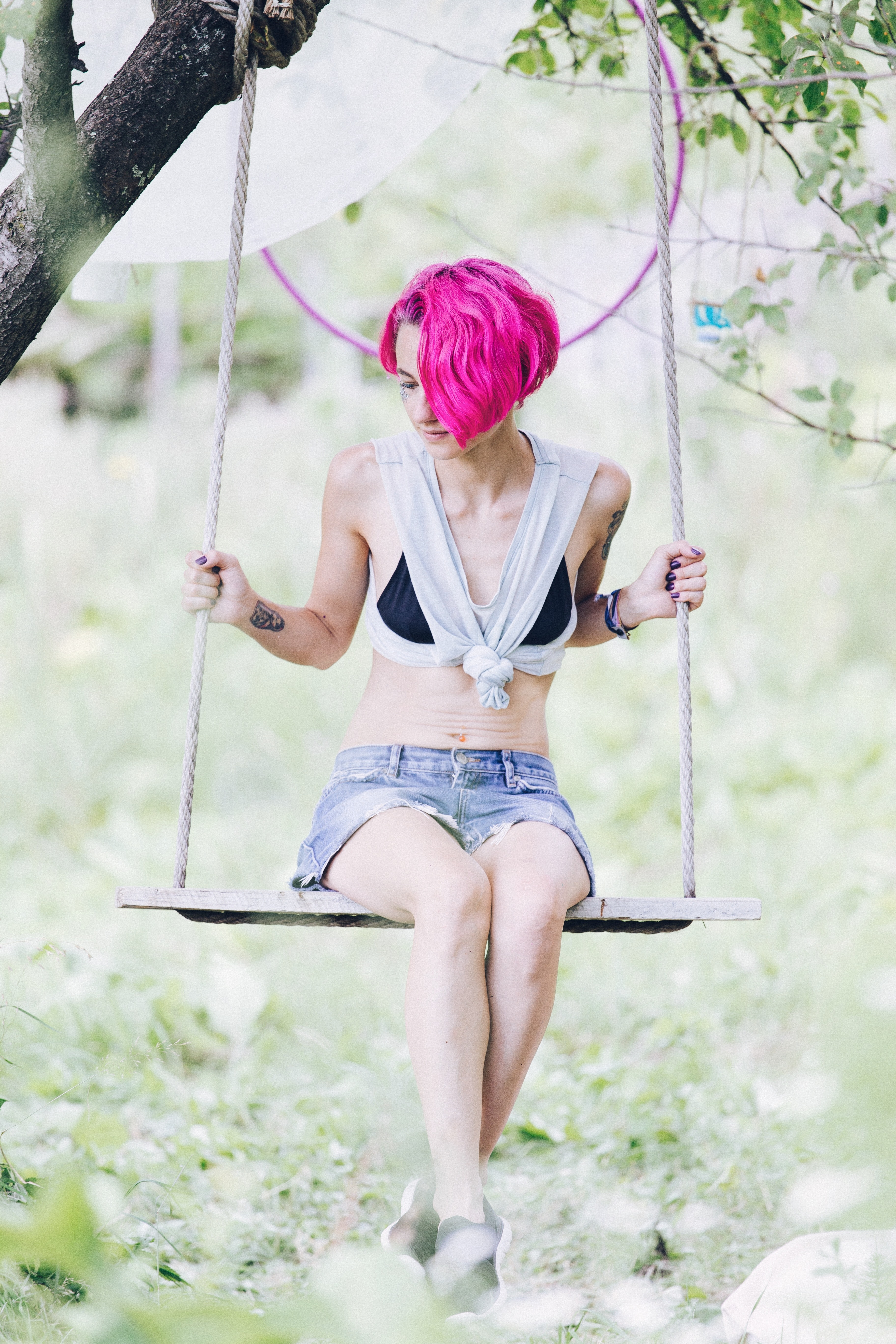 woman sitting on swing under tree during daytime