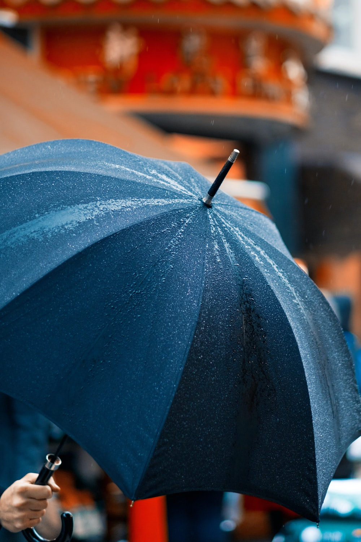 person holding umbrella while raining