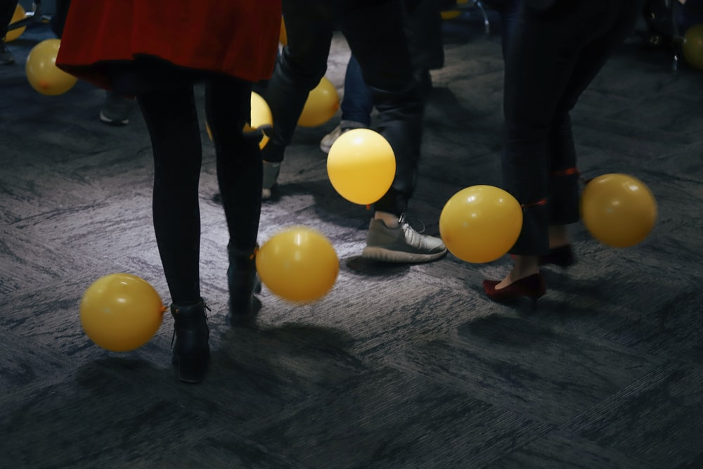 people standing near yellow balloons