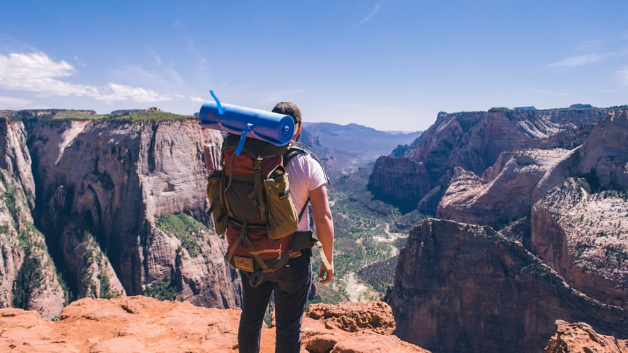 man with hiking backpack standing on a mountain