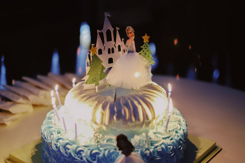 2-layer cake with lighted candles and Disney Frozen Queen Elsa cake topper