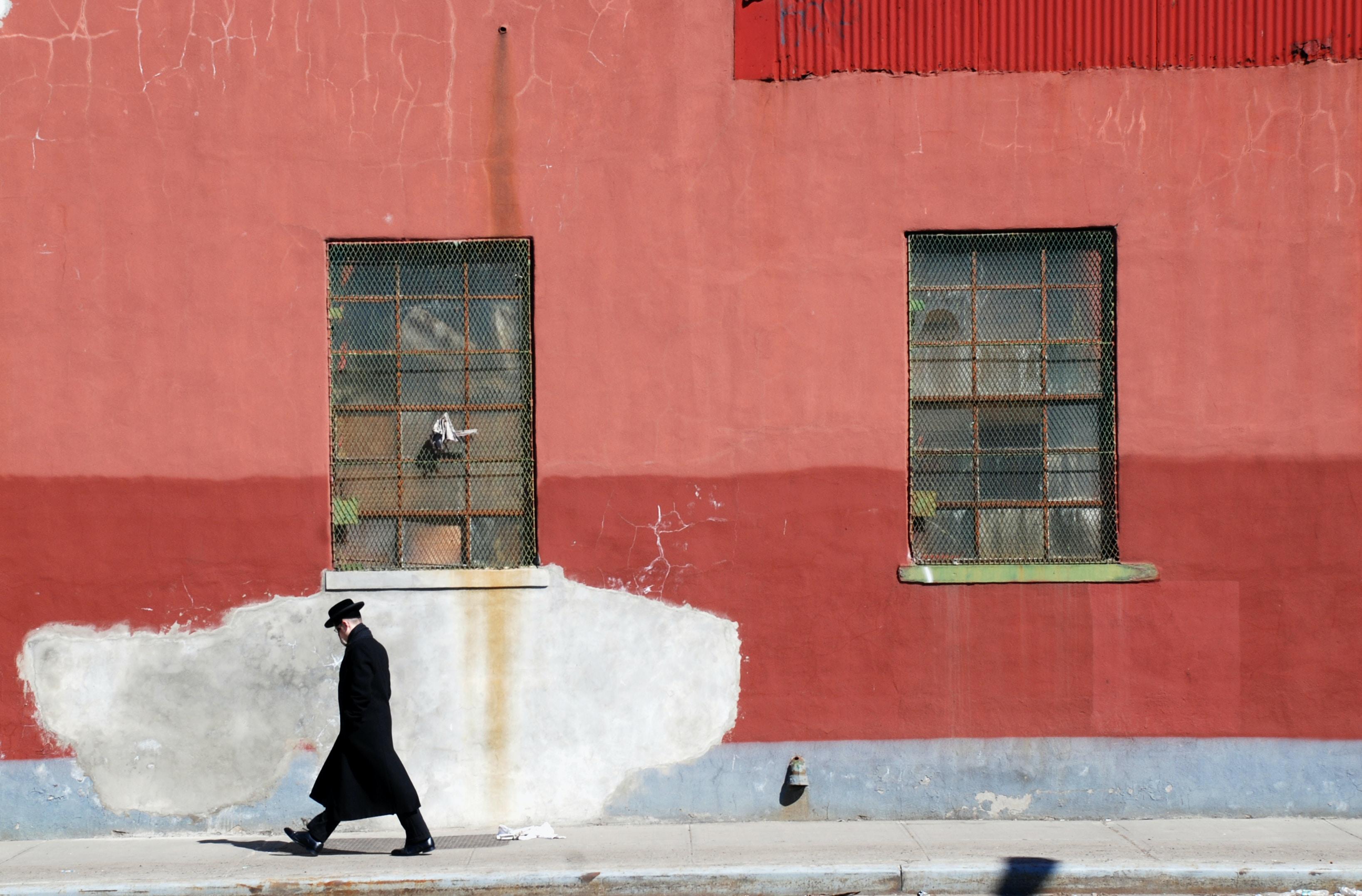 man walking beside red wall