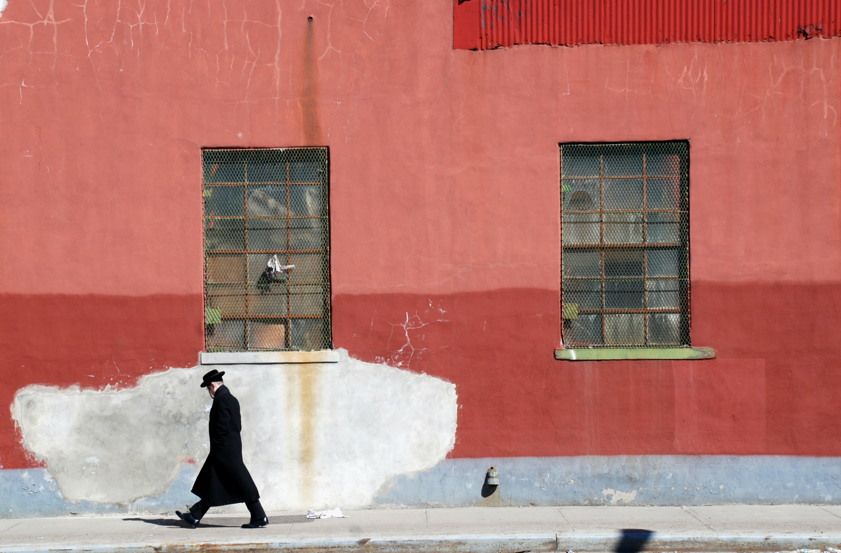 man walking beside red wall
