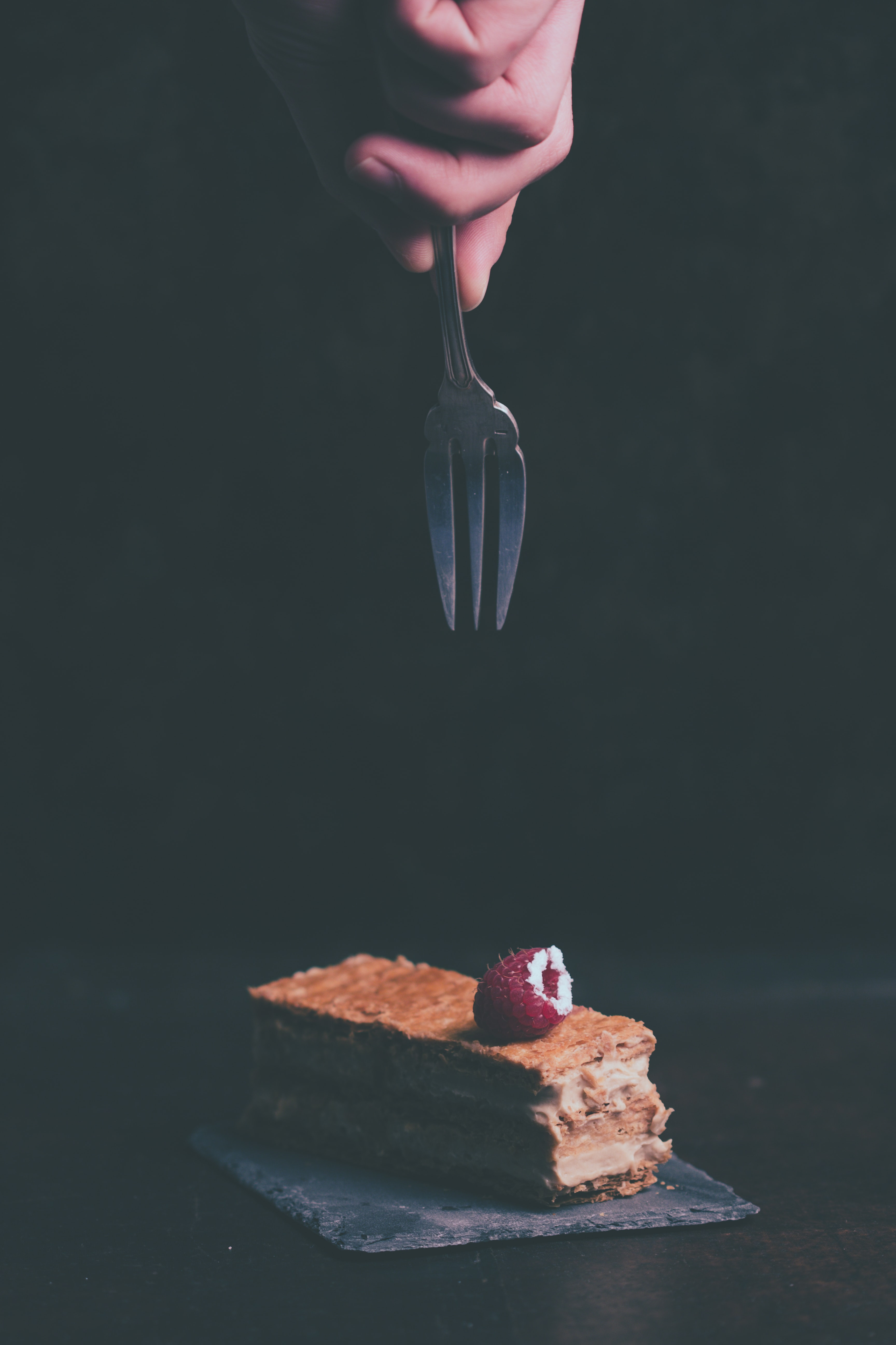 person holding fork about to grab cake