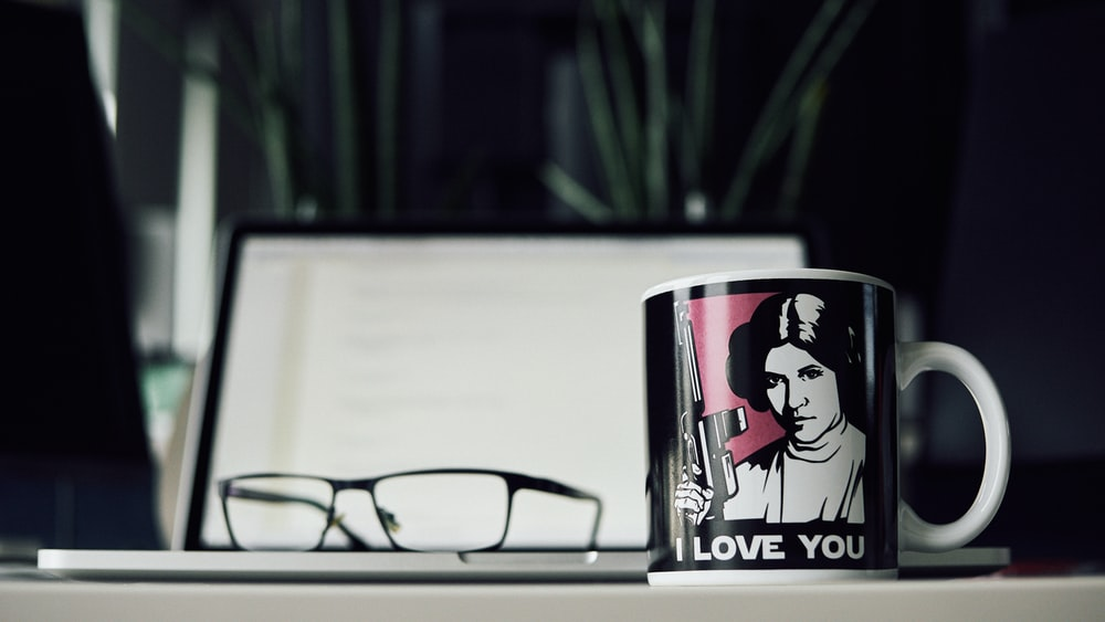 black and white ceramic mug beside reading glasse