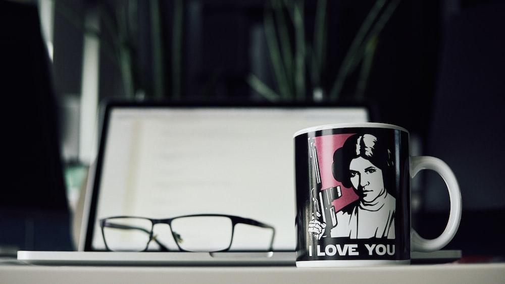 black and white ceramic mug beside reading glasse