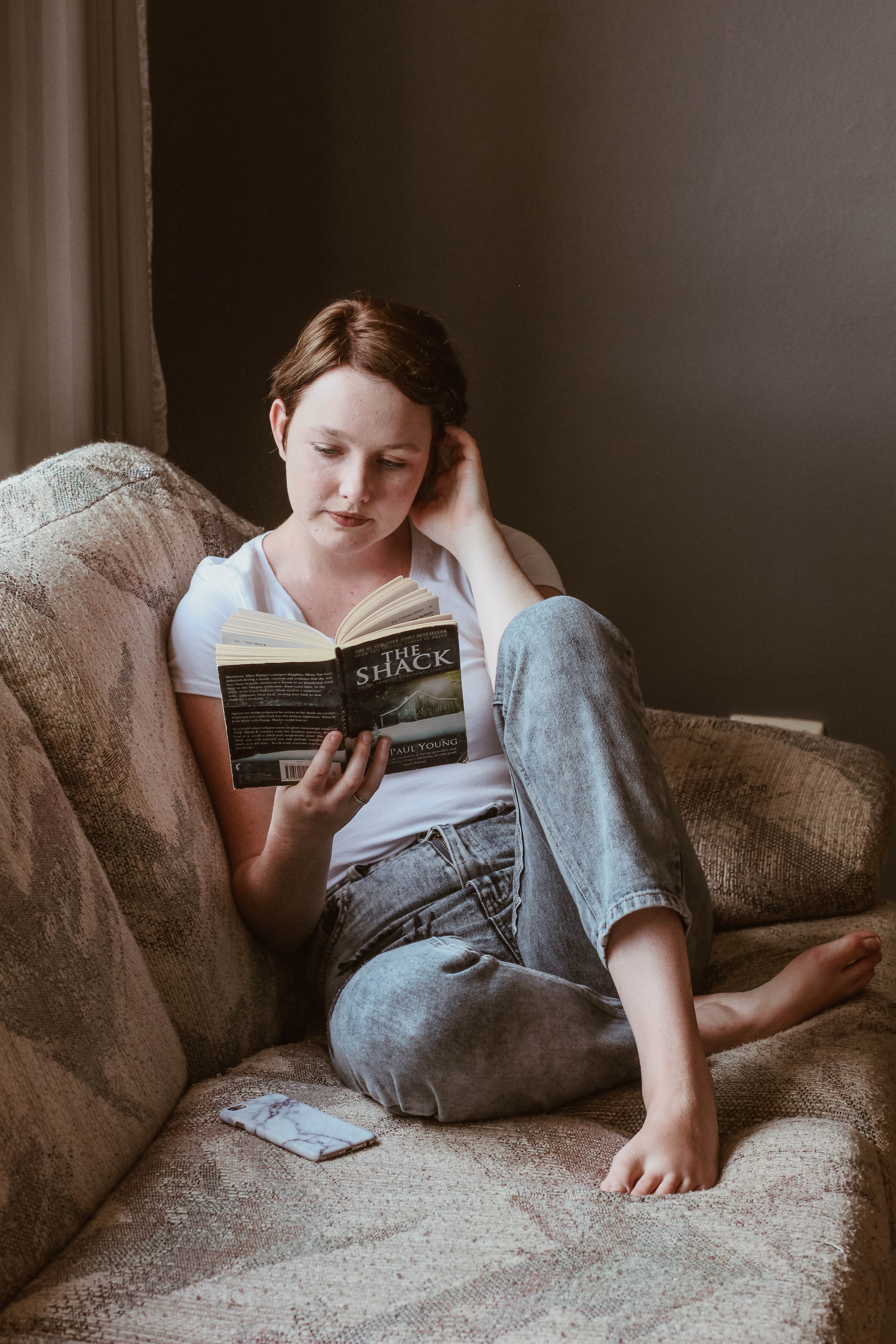 woman sitting on sofa while reading book inside room