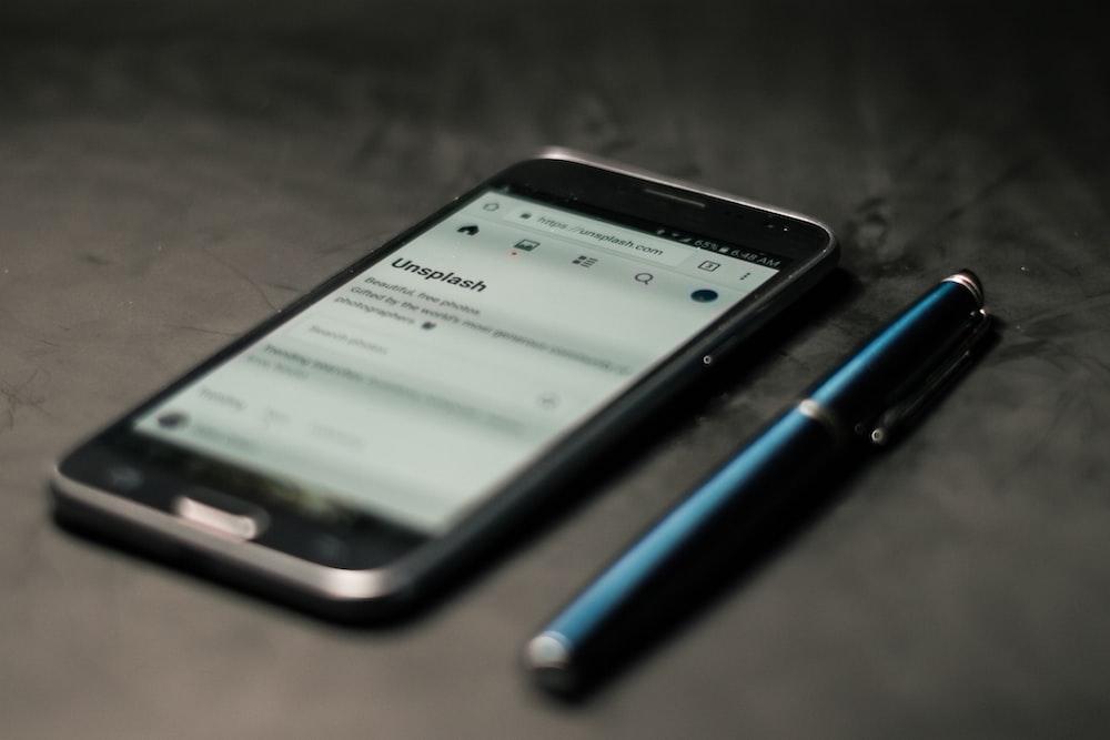 black smartphone beside pen