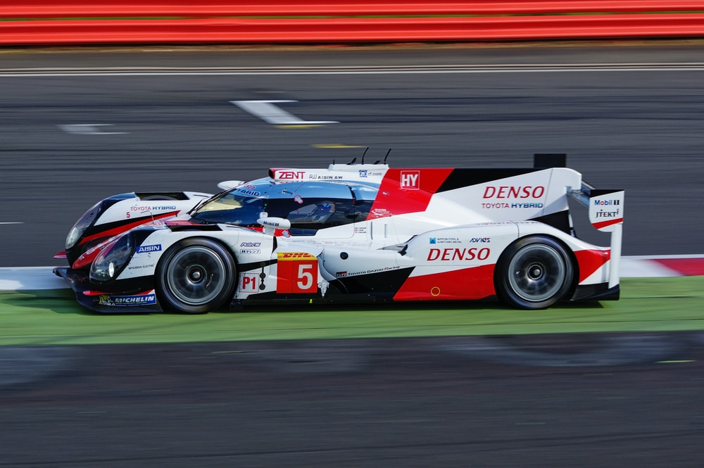 white and red denso supercar on racing field