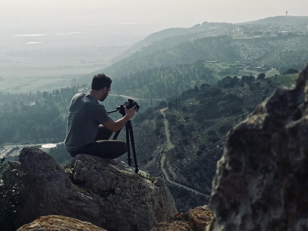 man sitting on rock using camera