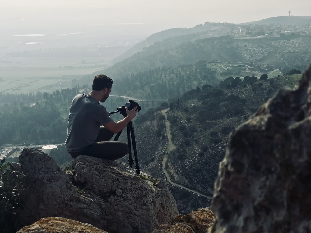 man sitting on rock using camera