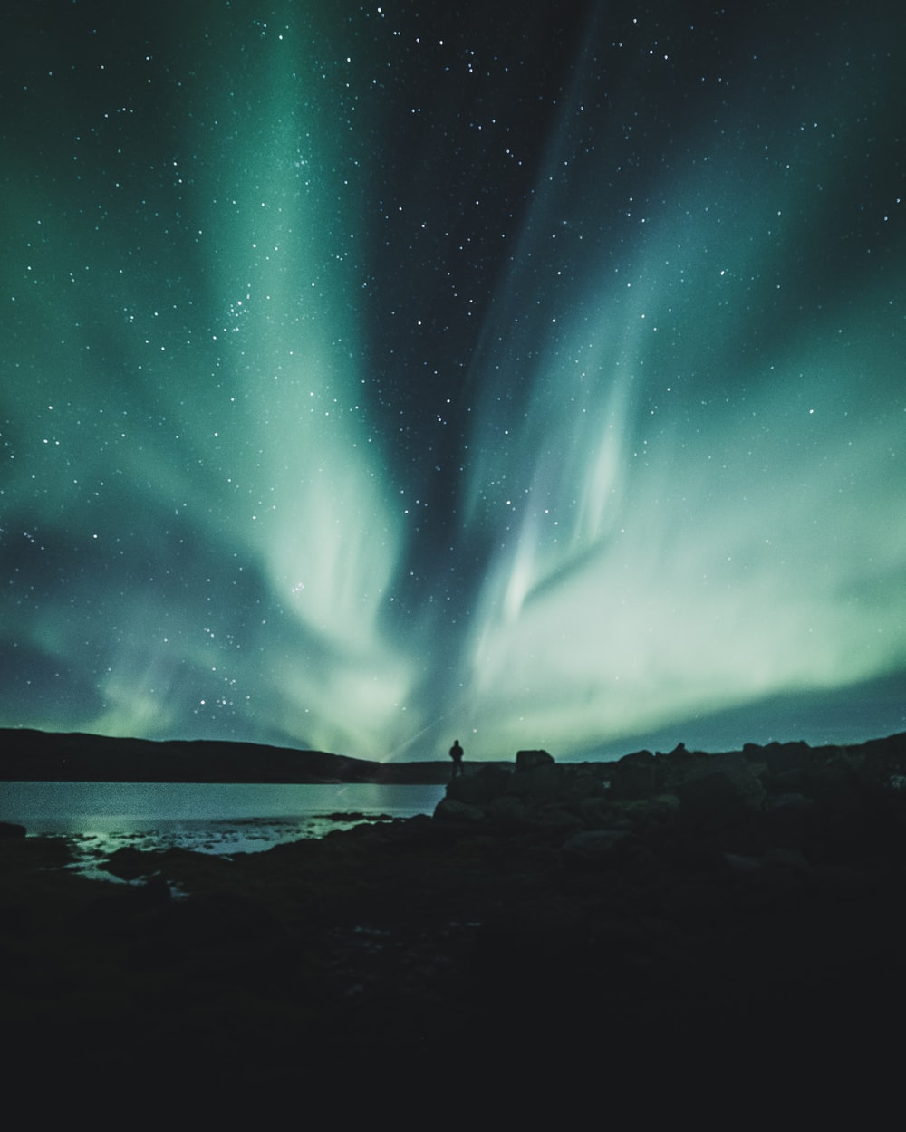 person standing near body of water during aurora northern sky