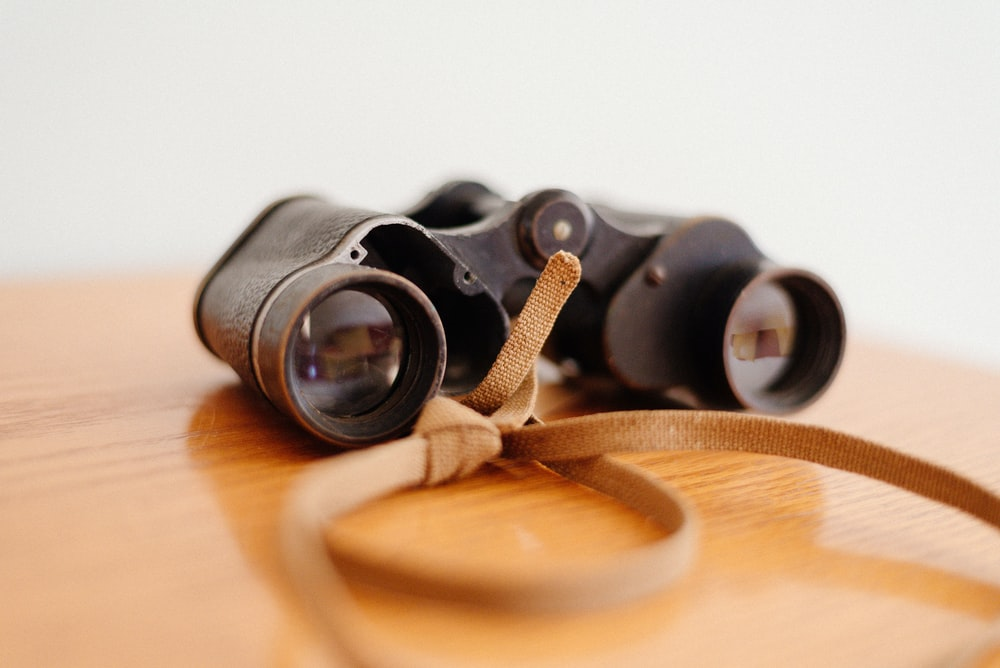 closeup photo of binoculars on brown wooden surface