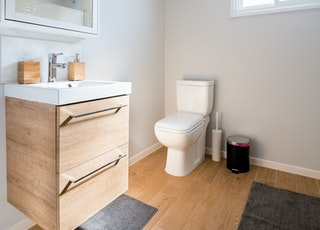white ceramic toilet bowl near vanity combo