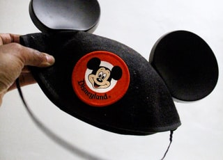 person holding Mickey Mouse cap